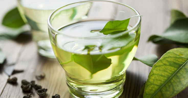 Natural Green Tea in Small Glass and Fresh Tea Leaves