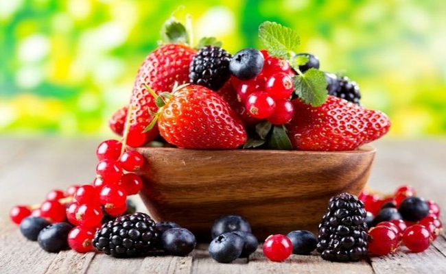 berries fruits in wooden bowl reccommended to be consumed by kidney stone patients
